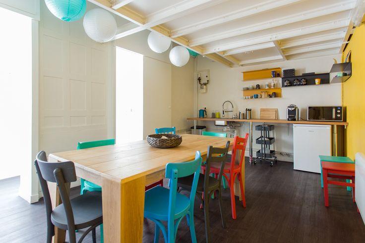 Coorpacademy - Plan de travail en chêne Etagères IKEA Table BUD Chaises de récupération repeintes aux couleurs de l'entreprise Sol synthétique