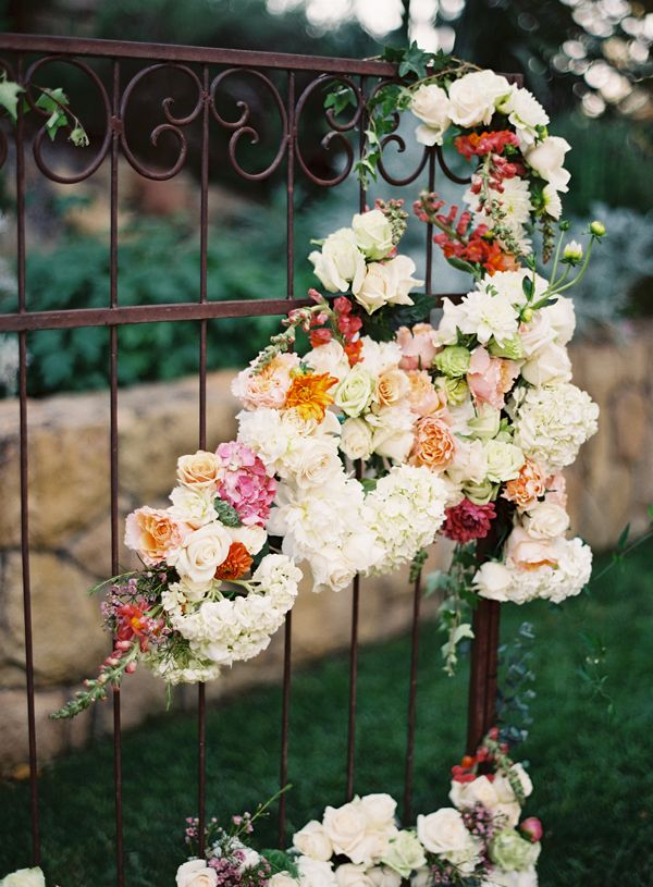 flowers on an iron gate. Lovely way to add outdoor wedding decor.
