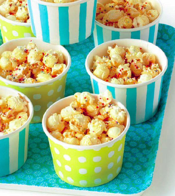 Verhit een laagje zonnebloem- of arachideolie in een pan met antiaanbaklaag. Strooi er een laagje maïskorrels (pofmaïs) in en evenveel kristalsuiker. Doe een deksel op de pan. Beweeg de pan een beetje heen en weer. Wanneer het poffen ophoudt, is je popcorn klaar. Doe de popcorn in een schaal, strooi er gekleurde spikkels over en schud goed om zodat de spikkels aan alle kanten aan de popcorn blijven plakken.  (per pakje heb je ongeveer 1 eetlepel maïskorrels nodig).