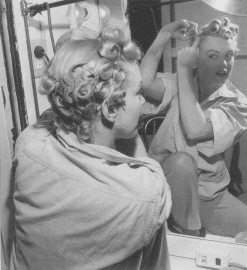 Marilyn Monroe pinning up her curls.    [1951]