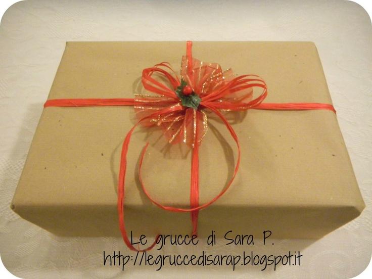 Pacco regalo con nastro di rafia rosso, organza dorata, fogliolina di pungitopo