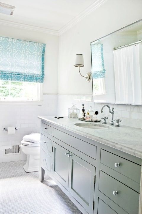 light grey bathroom vanity by queen, and light metal frame around mirror