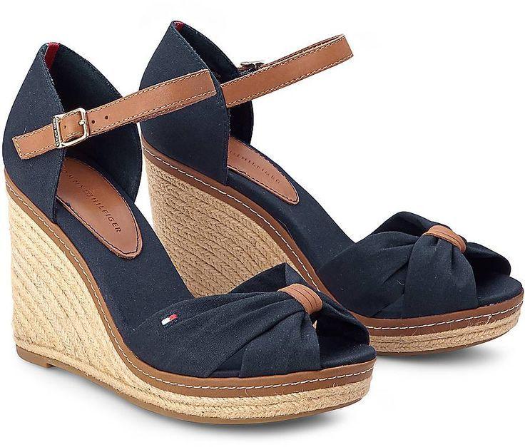 Eine Sandalette in sommerlicher Espadrilles-Optik aus der Tommy Hilfiger Kollektion. Canvas in Dunkelblau mit Leder-Riemen und blickfangendem Keil-Absatz aus Bast.