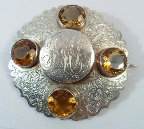 This is a mid 19th century Scottish mourning brooch, set with four facet cut citrines around a central compartment. Opening this reveals a lock of hair in the shape of a flower, embellished with thread. The reverse of the brooch has an open glass panel behind which is more hair. The front of the brooch is engraved all over with scrolls, and the cover of the locket is engraved with initials. It measures 5.2cm in diameter, weighs almost 27g, and is unmarked.Mourning Brooches, Mid 19Th, Cut Citrine, Central Compartments, Faceted Cut, Open Glasses, Glasses Panels, 19Th Century, Century Scottish