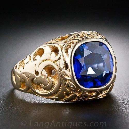 A majestic royal-blue cushion-cut sapphire, weighing 2.74 carats (but presenting somewhat larger due to a masterful lapidary), and accompanied by an American Gemological Laboratory certificate stating: Natural Corundum, No gemological evidence of heat, Origin: Cambodia (Pailin), radiates from within an 18 karat yellow gold mounting magnificently adorned with hand-pierced scrollwork. We repolished the sapphire and reset it in its original, and relatively understated, Victorian-era mounting. A…
