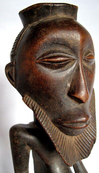 Oude man erachter - Kusu-DR Congo  Herkomst: Aangekocht door H. Westerdijk van G. Eertmans Antwerpen rond 1960Kusu cijfers hebben dezelfde algemene lay-out als hun tegenhangers van de Luba en Hemba. Meestal is Kusu echter de open kegelvormige top bedoeld om te bevatten een magische lading de figuur zijn om macht te geven. De serene uitdrukking van het gezicht en de fijne baard zijn hier kenmerkend voor Kusu sculptuur van permanent mannelijke voorouders. Hoewel halffigures domineren de…