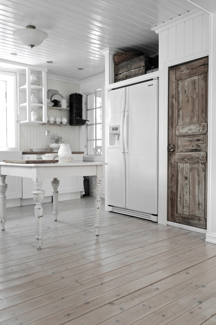 Muted kitchen with hardwood floors and white table and shelves