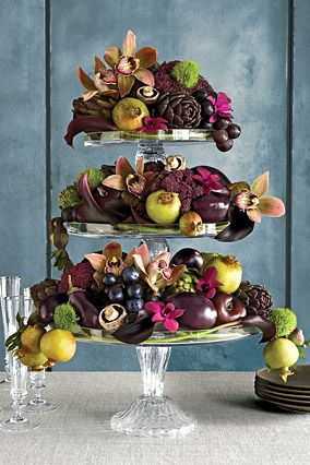 Mix fruits and flowers, including orchids, calla lilies, mushrooms, eggplant, and unripe pomegranates onto a tiered stand