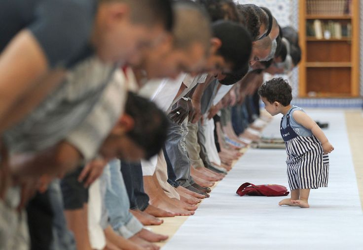 A child walks near members of the Muslim community attending midday prayers at Strasbourg Grand Mosque in Strasbourg, France on the first day of Ramadan, July 9, 2013.