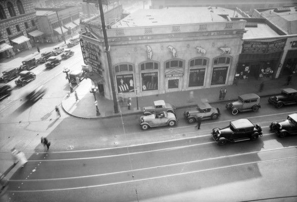 1933 view of the southwest corner of the intersection. By the time of this photo, a fur shop had replaced the Hellman Bank branch as the building's primary tenant. Courtesy of the Dick Whittington Photography Collection, USC Libraries.