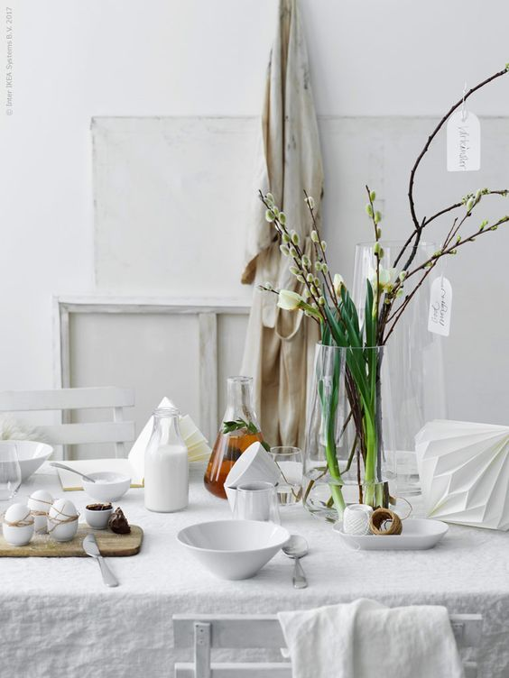 Easter Decoration, dining room table for the Holiday. Decorate with eggs, feathers and flowers with white Scandinavian interior