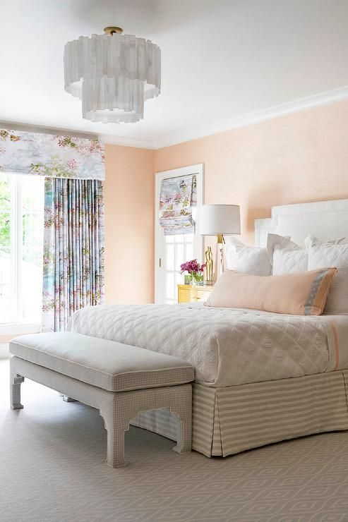 Restful peach pink bedroom features a gray plaid bench placed on     Restful peach pink bedroom features a gray plaid bench placed on gray  carpeting in front of a bed accented with a gray striped bed skirt and