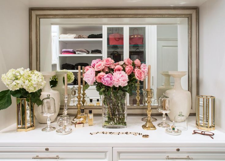 Collected candlesticks and fresh flowers create a pretty display in the vanity area of this custom closet in a London loft. Accessories do double duty as storage, including glass cloches that display rings, necklaces and bracelets.