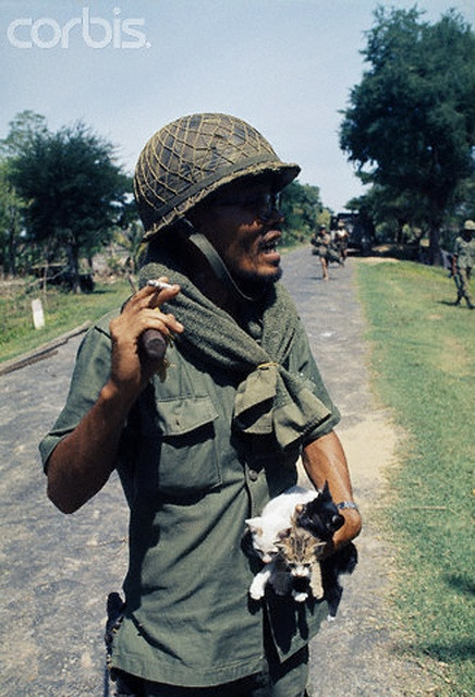 1974, Cambodia. Since the Lon Nol coup in March 1970, two groups are fighting for control - the Khmer National Armed Forces (FANK), supported by the USA, and the Army of the Republic of Vietnam (ARVN), pitted against the Cambodian People's National Liberation Armed Forces, (composed of Maoist nationalists and Khmer Rouge communists) supported by North Vietnam and the Vietcong. Government soldier with kittens. Image by © Patrick Chauvel/Sygma/Corbis