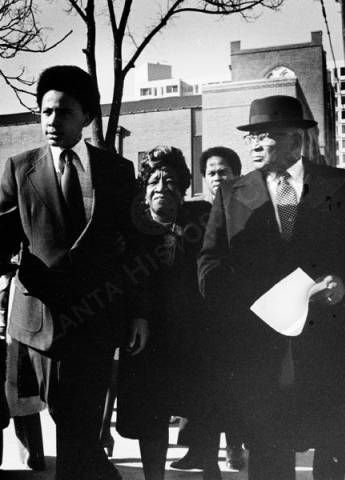 View of (L to R) Dexter King, son of Dr. Martin Luther King, Jr.; Alberta Williams King, mother of Dr. Martin Luther King, Jr.; unidentified; and Martin Luther King, Sr. walking along Auburn Avenue with Ebenezer Baptist Church in the background. Atlanta History Center.