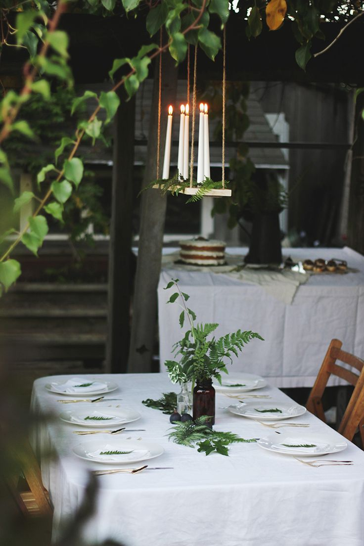 Candles on a floating shelf strewn with ferns