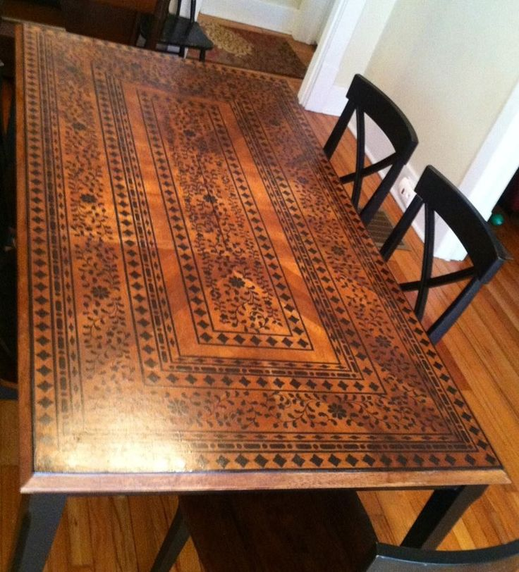 A stained table top gets updated with an all over black stencil pattern