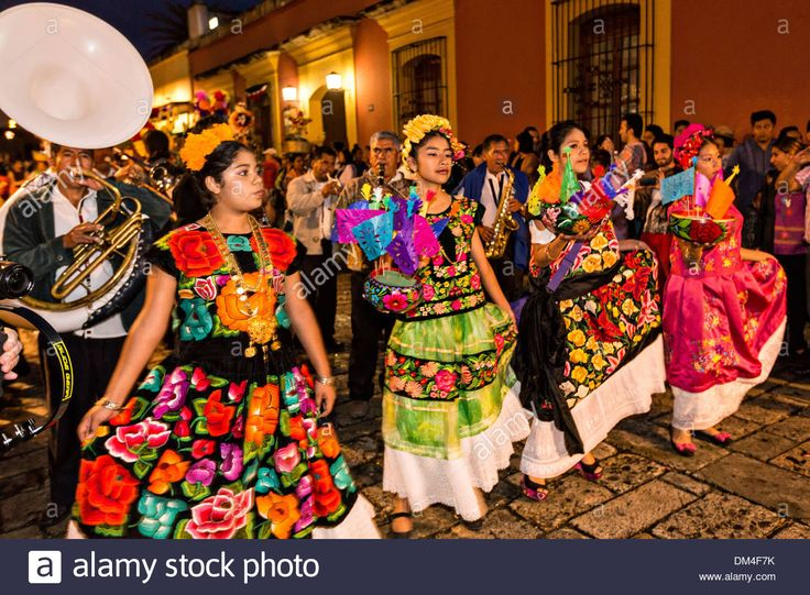 Young women dressed in traditional costumes parade in a comparsas past the Santo Domingo de Guzmán Church during the Day of the Dead Festival known in Spanish as Día de Muertos on November 2, 2013 in Oaxaca, Mexico. Stock Photo