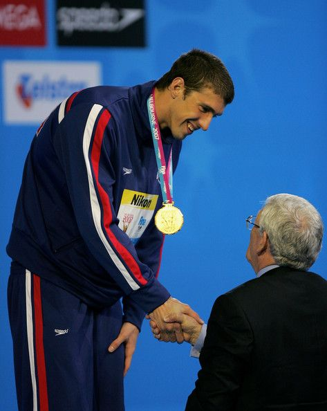 Michael Phelps Photos Photos - Michael Phelps of the USA receives his gold medal following his win and new world record in the Men's 200m Butterfly Final during the XII FINA World Championships at the Rod Laver Arena on March 28, 2007 in Melbourne, Australia. - XII FINA World Championships - Day 12