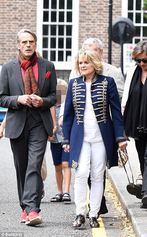 Jeremy Irons, left, appeared to feel a chill as he arrived wrapped up in a scarf to the event with wife Sinead Cusack