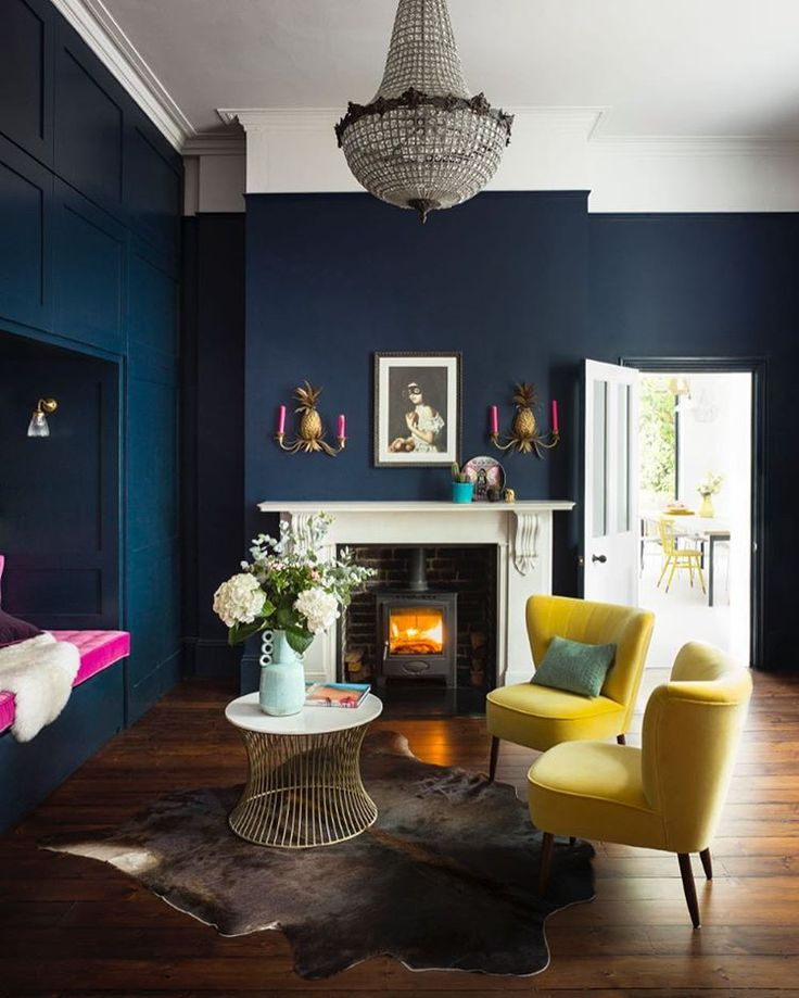 The fireplace, the pineapple sconces, the yellow and pink velvet, the deep  navy walls - so much to list after in this incredible living room.