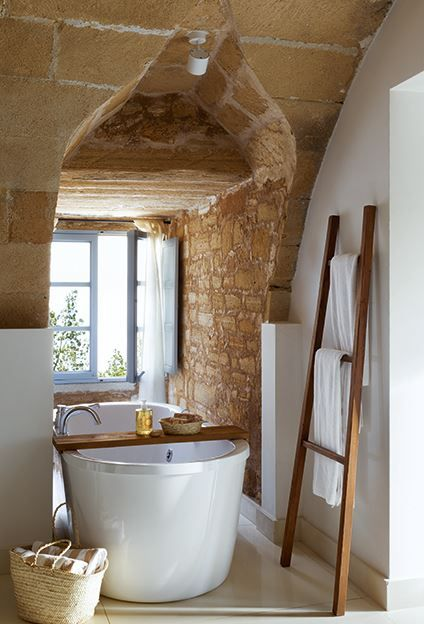 Love the rock wall, the old ladder used as a towel rack, and the wonderful little tub.: