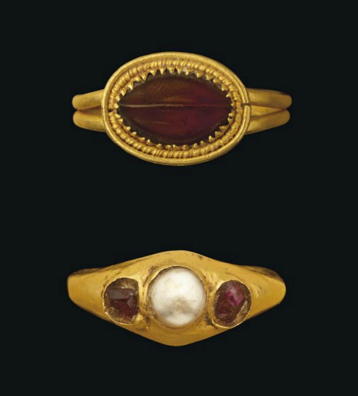 TWO ROMAN GOLD RINGS   CIRCA 1ST-3RD CENTURY A.D.   One with oval garnet with central raised rib, two shorter incised lines either side, in claw-set bezel edged with spiral-beaded and plain wire, hoop modern; and another gold ring, the plain hoop widening to a hollow raised bezel set with later garnets and central pearl  ¾ in. (2 cm.) and 7/8 (2.3 cm.) wide; ring size I and N respectively