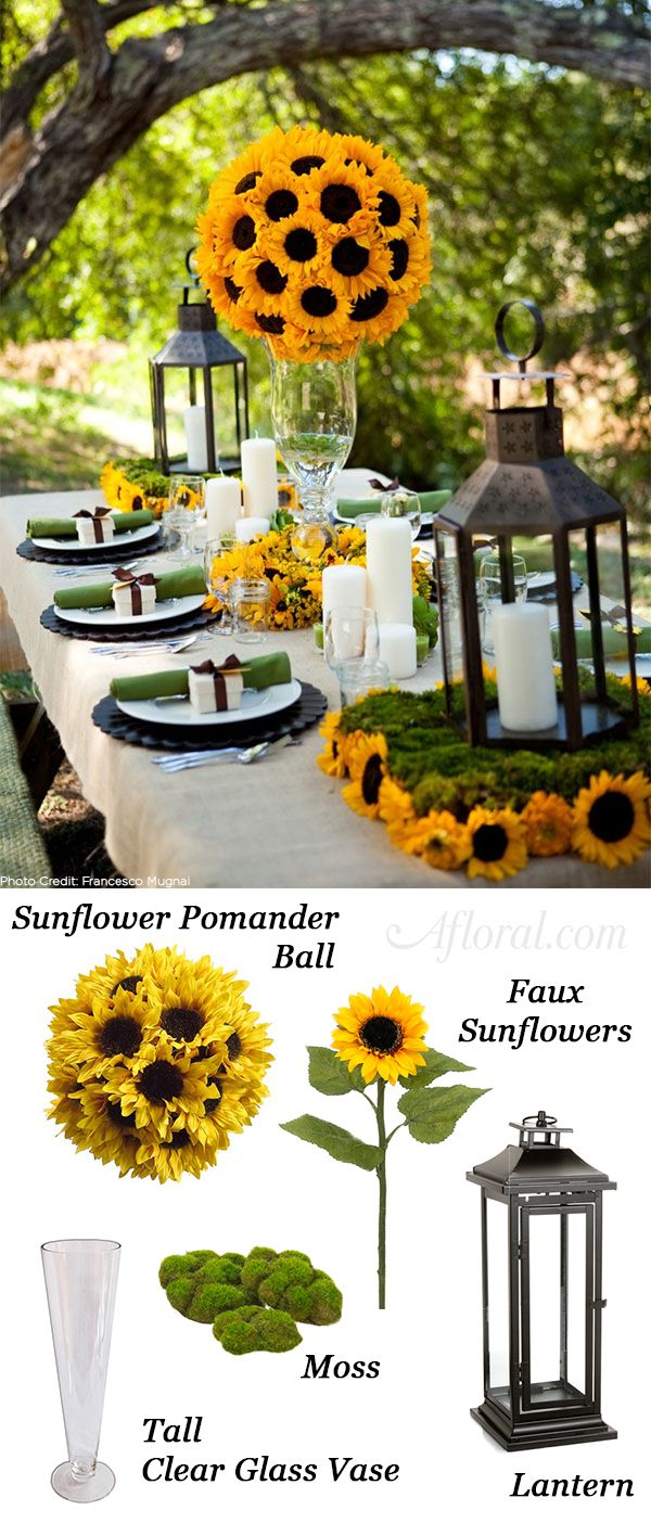 Create an elegant summer tablescape with towering sunflower centerpieces and low moss and floral arrangements.  Create this look for less with silk flowers from Afloral.com.  To DIY this look on a budget your a mini sunflower bush and moss, attached to floral foam, as a base for lanterns.  Create a tall centerpiece with a pre-made sunflower pomander placed on top of a tall clear glass vase.  Create romantic lighting with simple white pillar candles.  Find everything you need at Afloral.com.