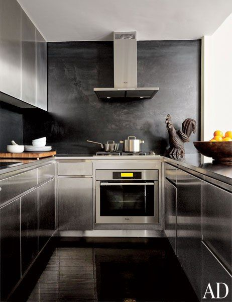 The stainless steel kitchen has a Miele oven, cooktop, and hood along with stainless-steel cabinetry and a blackened-steel backsplash; the carved folk-art rooster is 19th century.