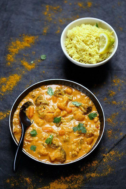 Curry végétarien 50 cl de lait de coco 300 g de tomates en boîte 3 gousses d'ail 250 g de fleurs de chou-fleur 250 g de fleurs de brocoli 200 g de carottes en morceaux 3 gousses d'ail 2 cm de gingembre frais, coupé en dés 30 g de noix de cajou mixées une banane 1 gros oignon jaune 1 piment oiseau épices : 3 càs bombées de curry en poudre (de qualité), 1 càc de coriandre, 1 càc de curcuma, 2 gousses de cardamome verte, une pincée de cannelle, une pincée de cumin en poudre huile végétale sel