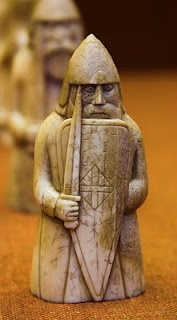 The Lewis chessmen are a group of chess pieces discovered on the Isle of Lewis in 1831. They were carved from walrus ivory and whale teeth in the 12th Century in Norway. There are 78 pieces: 8 kings, 8 queens, 16 bishops, 15 knights, 12 rooks, and 19 pawns, from as many as 5 different sets. Unlike modern chess sets, the rooks are portrayed as soldiers, including four berserks, chewing their shields, while the pawns are small geometric pieces, resembling standing stones.