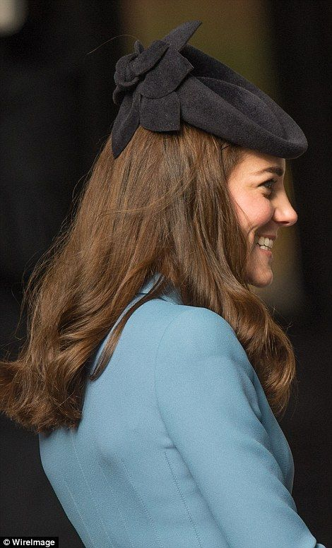Portrait of a princess: Kate showcases the detail of her Lock and Co hat from the back as she smiles a cheeky grin