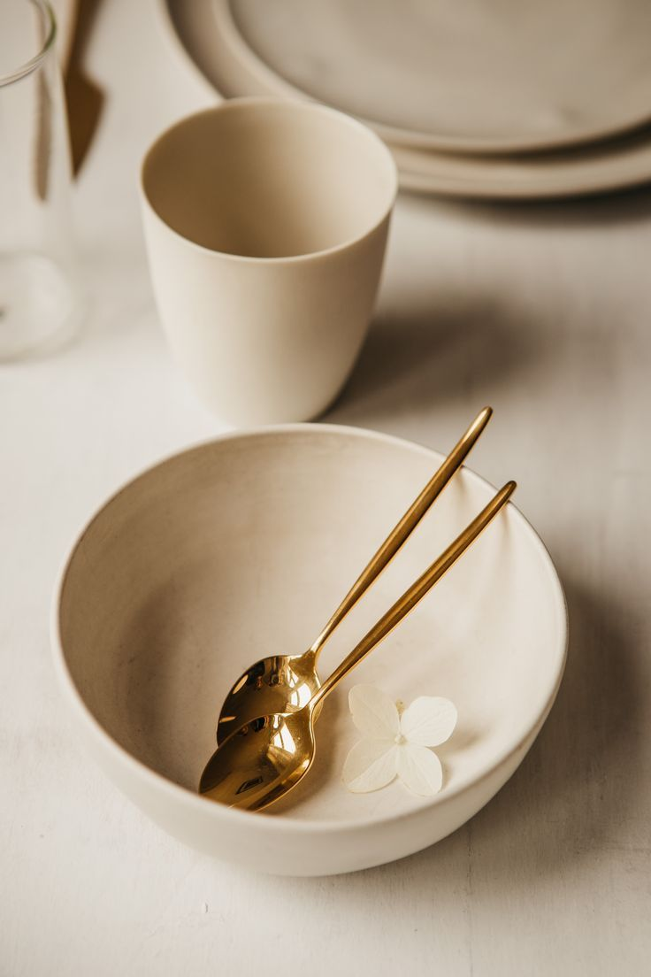 Natural and light stoneware, golden Cutipol cutlery on whitewashed wooden table. Wedding table design inspiration by Hilde.
