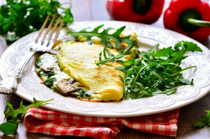Omelet stuffed with spinach and mushrooms on a white plate.