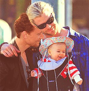 D'awwww..... Tom Hiddleston, Chris Hemsworth, and baby India Hemsworth <3. I just bask in the adorableness of Thor wearing a baby carrier with a baby in a floral bonnet--and that Loki just happens to be there, too, lololol