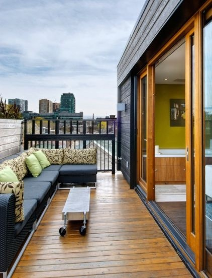 On warm days, the couple opens up the rooftop space to the surrounding views and relaxes on the outdoor sectional, made by Toronto's Andrew Richard Designs. T