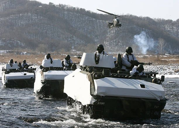 South Korean army K-200 armoured vehicles cross a river during a regular winter drill in Yeoncheon south of the demilitarised zone, which divides the peninsula, 23 January 2008. The two Koreas are still technically at war despite a decade of rapprochement during liberal governments in the South.