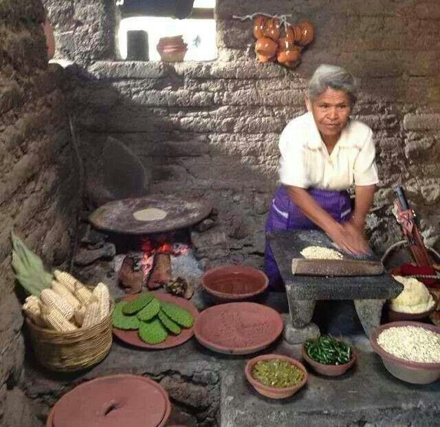 """Hermosa fotografía de mujer haciendo tortillas. - TRULY making tortillas """"from scratch""""! First she makes the """"nixtamal"""" (dried corn soaked overnight in hot water with """"cal"""" (lime), then the softened husked kernals are ground by hand on the stone """"metate"""" with a stone """"mano"""". Water is added then to make the """"masa"""" (dough), which is then shaped entirely by hand from balls into flat round tortillas by patting them back and forth between her well-callused hands. Sabrosissimas! (Delicious!)"""