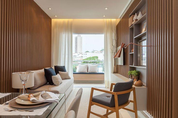 Decoração de apartamento pequeno e charmoso com ambientes integrados com ripas de madeira. Na sala sofá, poltrona de madeira, plantas e luz natural.