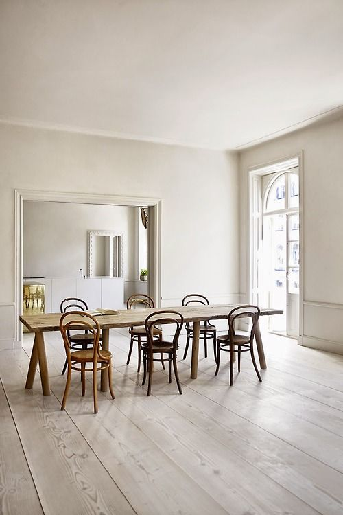 Simple interior, blonde wide plank wooden floor, Thonet chairs, dinning room, arched window, simple wooden table, classical detail, kitchen