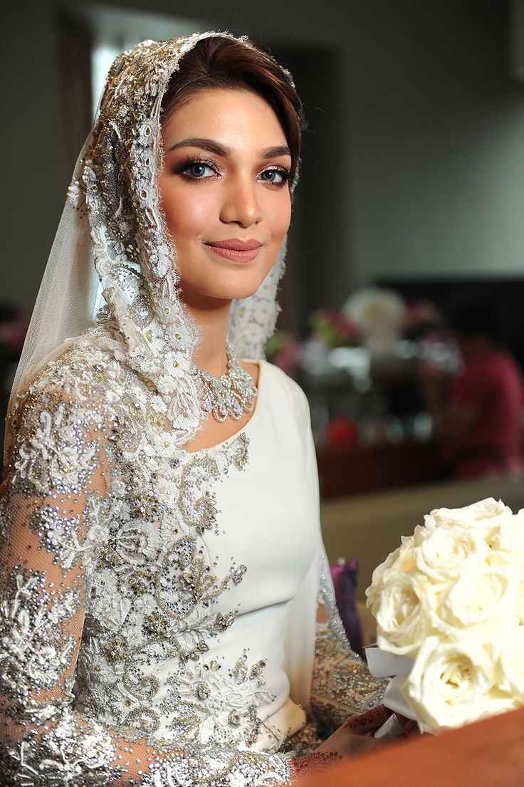 White wedding sheath gown with delicate grey floral detail on veil and dress // Malaysian TV personalities Amar Baharin and Amyra Rosli tied the knot in a lavish nikah (solemnisation ceremony) in Kuala Lumpur, Malaysia. The bride wore a jaw-dropping bespoke blush ball gown made of French lace and Swarovski crystals, while the groom looked every part the knight in shining armour in his Prince Charming-inspired suit by Rizman Ruzaini Creations. Here, we take you inside this celebrity couple's…