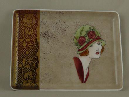 Ce petit plateau en porcelaine est décoré d'un visage de femme des années 20, sur un fond café au lait moucheté de brun rouge... Sur le côté gauche, une bande en dégradé d - 16378516