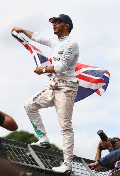 Lewis Hamilton Photos - Lewis Hamilton of Great Britain and Mercedes GP stands on top of a fence with a Great Britain flag to celebrate his win with the British fans during the Formula One Grand Prix of Great Britain at Silverstone on July 10, 2016 in Northampton, England. - F1 Grand Prix of Great Britain