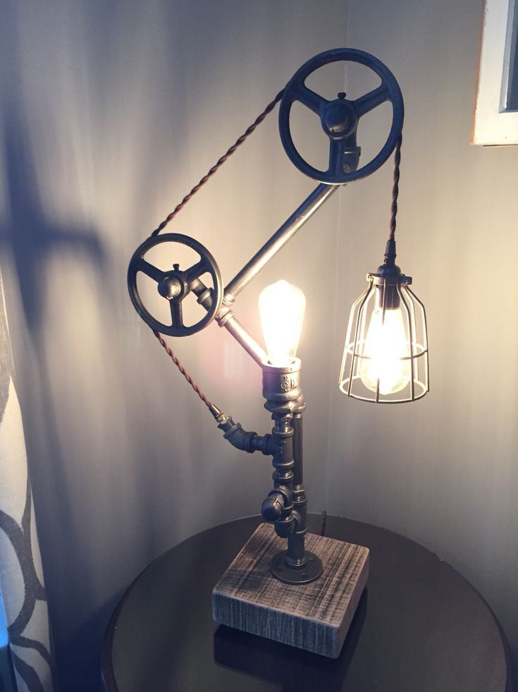 Industrial gas pipe and pulleys with Edison bulbs, cotton covered cord, light bulb cage, and a solid oak base.