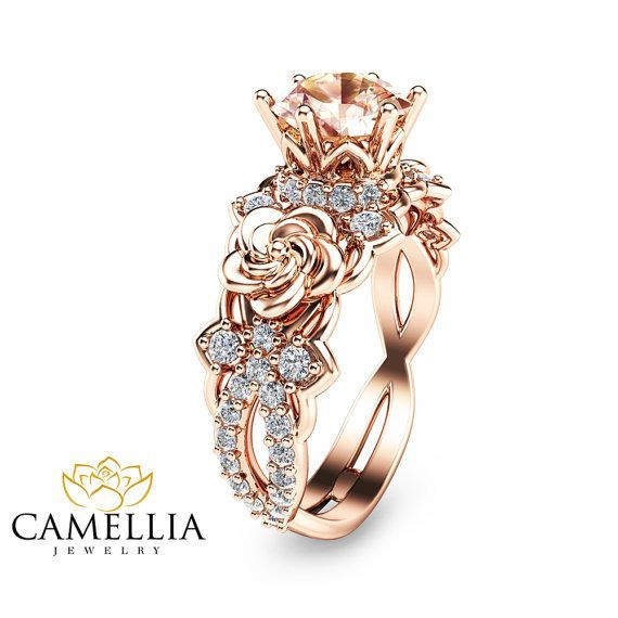 For impeccable style, you simply cannot go wrong with this 14K rose gold Morganite engagement ring from Camellia Jewelry. Hand-forged in stunning detail, the mounting resembles a flower deco as it elevates the floral accents and sparkling pink morganite stone in luminous detail. Dainty diamond accents add a measure of glamour to complete the design. Whether worn as a promise ring or an engagement ring, this unique morganite ring symbolizes an everlasting love that will only ripen with age…