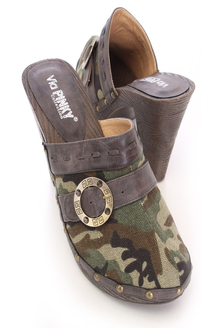 Get the style and comfort any woman loves. With its timeless clog design its sure to add flare to any ensemble. Pair them with a white tee and skinny jeans for a casual look thats not dull. This style features a clog design with a closed toe, camouflage canvas upper with a buckle strap accent, faux leather trim with a studded detail, faux wood heel, slip on, and stitch detailing. Approximately 4.25 inch heel 1 inch platform.