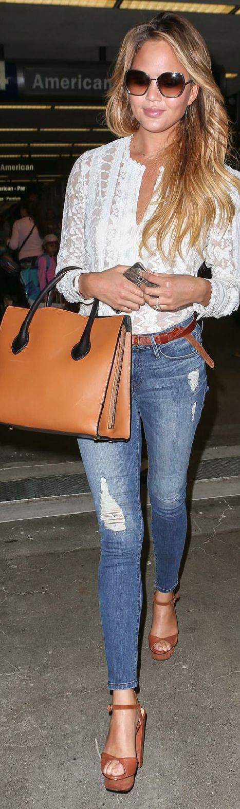 Chrissy Teigen at LAX in a Rebecca Taylor top paired with skinny jeans, a Céline brown leather tote, and Chloé sunglasses.