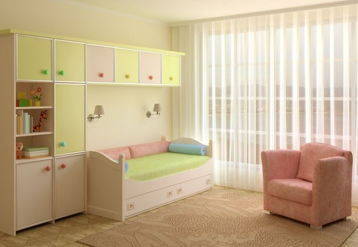 A lovely children's room with a day bed and pastel built-in storage. The textured light beige rug over the parquet flooring has a light pink chair with a similar pattern resting on it.