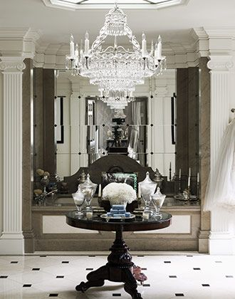 Gorgeous effect with the white columns &  millwork with glass mirror tiles and chandelier