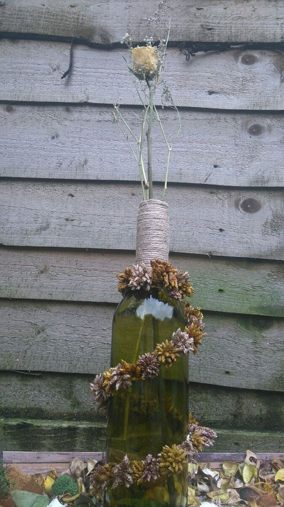 Dry flowers have their charm..When they swirl over an old bottle of wine result in a beautiful rustic piece of decor